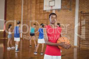 High school boy holding a basketball while team playing in background