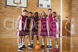 Confident basketball players standing with arms around in the court