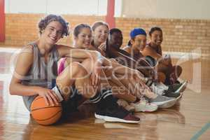 High school kids sitting on the floor in basketball court indoors