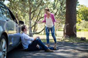 Woman shouting on man sitting by breakdown car