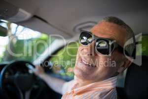 Portrait of smiling senior man wearing sunglasses in car