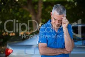 Tensed senior man standing by car