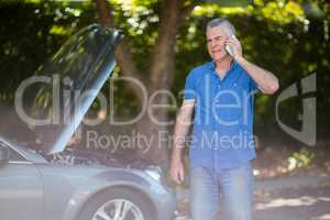 Senior man talking on phone by breakdown car
