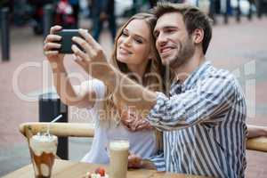 Couple holding smart phone while sitting at sidewalk cafe