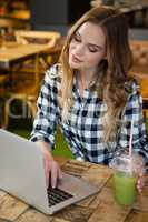 Woman using laptop at table in cafe shop