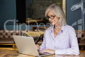 Senior woman using laptop computer while sitting at table