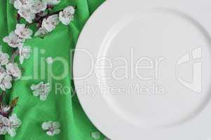 Empty white dish on a green napkin with cherry blossoms