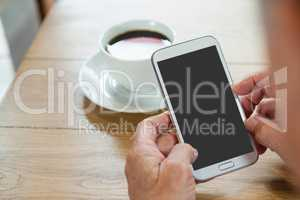 Close up of senior person holding smart phone while sitting at wooden table