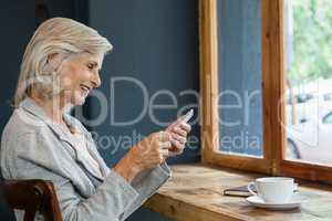 Smiling woman using smart phone while sitting at table