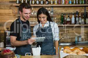 Waiter and waitresses using digital tablet at counter