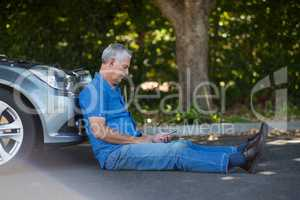 Senior man sitting by car on road