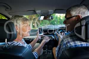 Couple discussing over phone while sitting in car