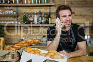 Waiter talking on mobile phone at counter
