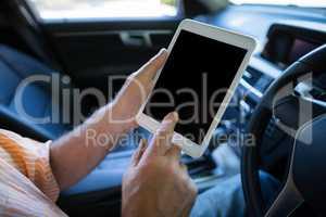 Man using digital tablet in car