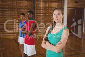 High school kids standing with arms crossed in the basketball court