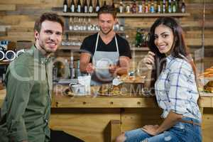 Portrait of couple sitting at counter while waiter serving coffee
