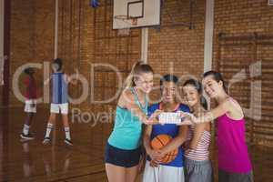 High school girls taking a selfie in basketball court