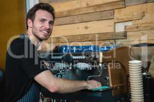 Portrait of smiling waiter cleaning coffee machine at counter