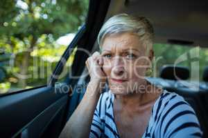 Tensed senior woman siting in car