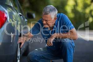 Nan checking wheel of car on road