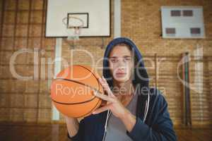 High school boy standing with basketball in the court