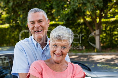 Smiling senior couple enjoying by car