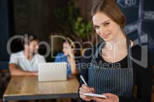 Portrait of owner writing on notepad