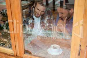 Friends sitting by window at cafe shop