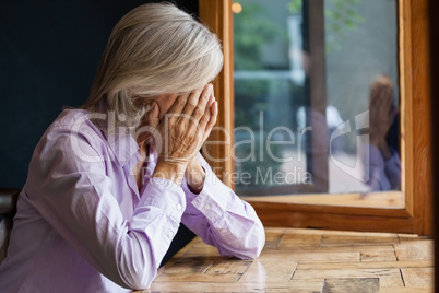 Senior woman covering face while sitting at table in cafe