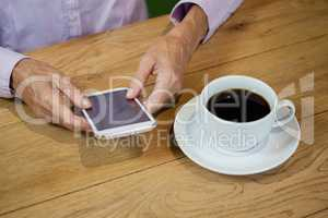 High angle view of senior woman using smart phone at cafe