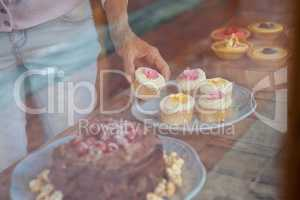 Midsection of woman holding cupcake while standing at table