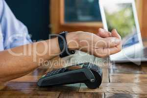 Close up of woman scanning smart watch on credit card reader