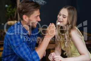 Smiling man feeding woman