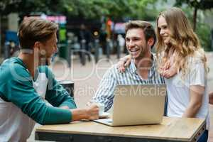 Cheerful couple looking at friend while sitting at sidewalk cafe