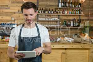 Waiter using digital tablet at counter