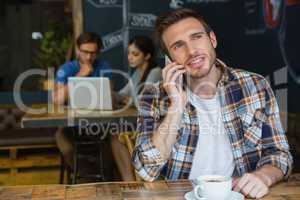 Man talking on mobile phone while having coffee