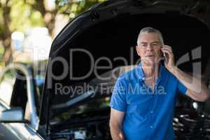 Senior man talking on phone after car breakdown