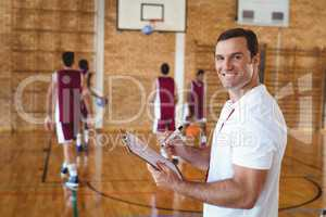 Basketball coach holding clipboard in the court