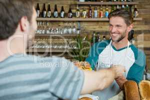Smiling waiter serving to customer at counter