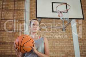Determined girl holding a basket ball