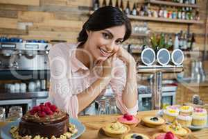 Portrait of waitress leaning at counter