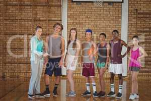 Female coach and high school kids standing in basketball court