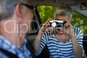 Woman photographing man in car