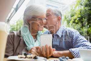 Senior man kissing woman