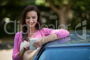 Woman using mobile phone while standing by car