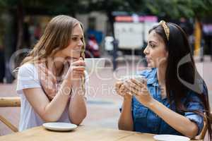 Friends drinking coffee while sitting at sidewalk cafe