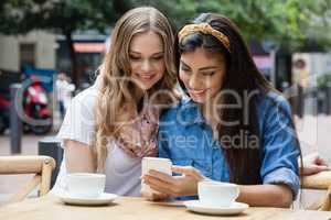 Happy friends drinking coffee while using smart phone at sidewalk cafe