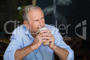 Senior man looking away while holding cold coffee