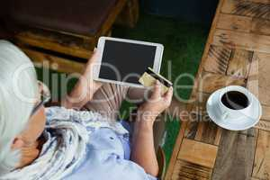 High angle view of woman holding tablet and credit card