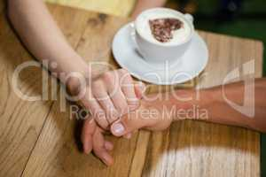 High angle view of couple holding hands by coffee cup